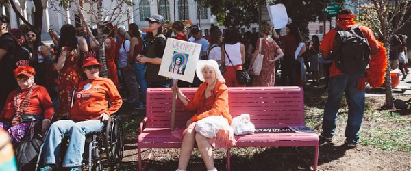 image of woman in orange shirt and white hat holding a placard, crowd standing behind her