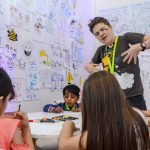 Photo of Aska in a classroom with three children drawing