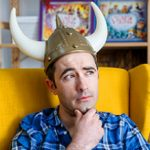 Image: Author and illustrator, James Foley, sitting in a large chair, hand on chin and wearing a viking hat