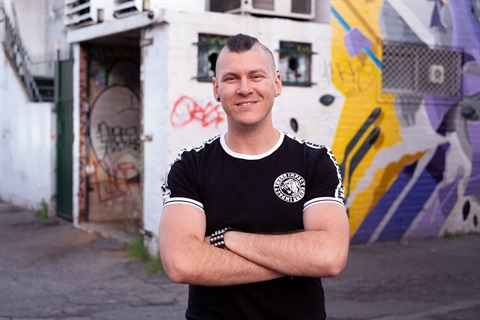 Image: author Holden Sheppard, smiling, arms crossed, standing in front of a graffitied building