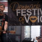 Image of a male performer with a guitar next to a banner reading 'Denmark Festival of Voice'