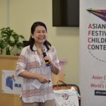 Woman speaking into a microphone with Asian Festival of Children's Content banner next to her.