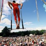 Image: an aerial acrobat on a high swing above a crowd.