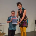 Young child receiving an award for best entry in a science writing competition