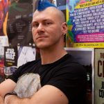 Image is of Holden Sheppard who has a blue mohawk standing in front of a wall filled with posters.