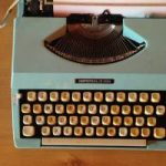 Image of an old fashioned typewriter on a wooden desk
