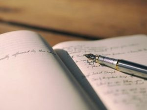 Image of a notebook with writing in it. A pen with a nib rests on top of the page