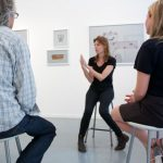 Artist Katie Breckon talking to a group of people with art work on the wall behind her.