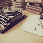 Image is of an old fashioned typewriter sitting on a desk. Next to it is some paper and a pen.