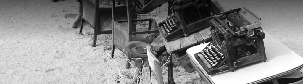 Image is a black and white photo of wooden chairs and tables with typewriters sitting on them.