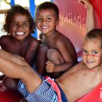 Image is of three Indigenous boys sitting in plastic play equipment and grinning at the camera.