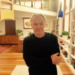 Image: Author Tony Birch standing in a large room with wooden floors and lined with bookshelves.