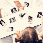 Image is a bird's eye view of a young girl looking down at a photo album containing a set of polaroid photos.