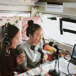Image is of two young girls in a caravan. They have headphones on and are talking into microphones.