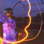 Image Description: A young man with dark hair is wearing a VR Mask. He is outside and swirls of light are coming out of the instrument he is holding.
