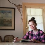 Image description: Maddie Godfrey wears a checked shirt and sits at a large table. They are looking at the camera. Their hands hold a pen and notebook open on the table.