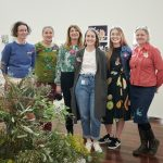 Image description: a group of women stand in an art gallery and smile at the camera. In the foreground is a display of native flowers, which are represented in a painting on the wall behind.