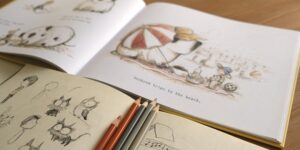 Image description: Two picture books with illustrations by Gabriel Evans lie open on a table. Five pencils lie flat across the bottom book.